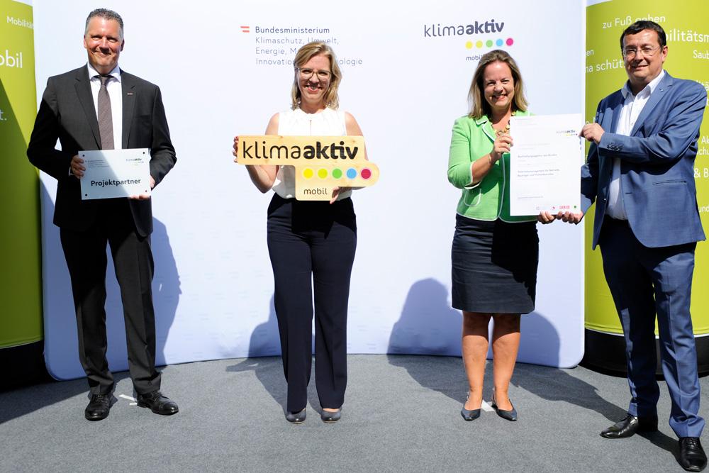 Leonore Gewessler und Alexander Klacska, Obmann der Bundessparte Transport und Verkehr der WKO, überreichen die Auszeichnung für die BHAG an Dr. Angelika Schätz und Andreas Böhm. (Foto: BMK/William Tadros)